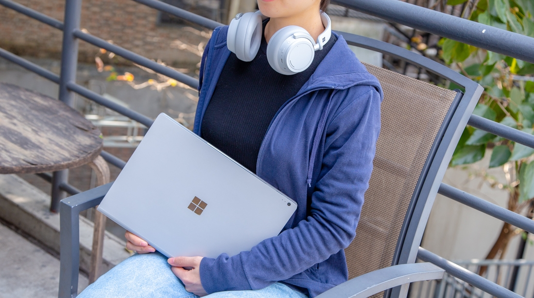 Surface laptop and headphones around girl neck